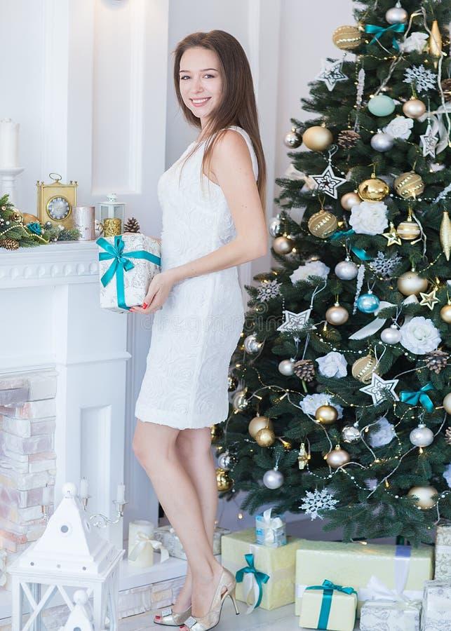 Stående av den härliga unga kvinnan med gåvan på bakgrund ny Ye royaltyfri foto