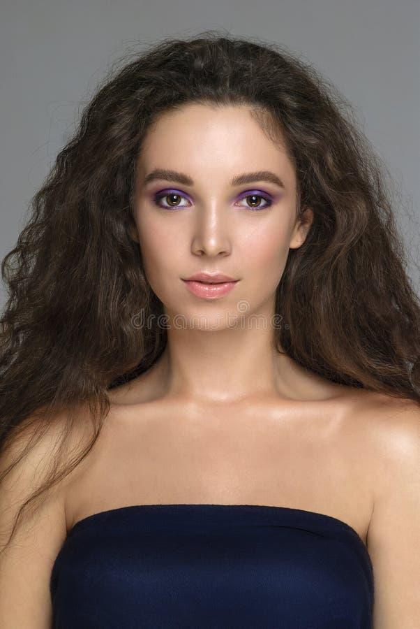 Stående av den härliga unga kvinnan med idérik makeup med krullningen royaltyfria foton
