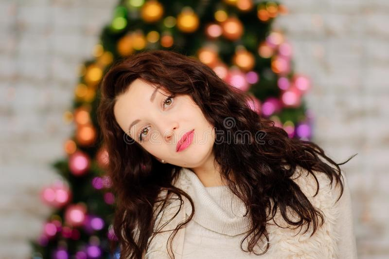 Stående av den härliga unga kvinnan med långt mörkt hår nära den suddiga julgranen med färgrika Glass bollar royaltyfria bilder