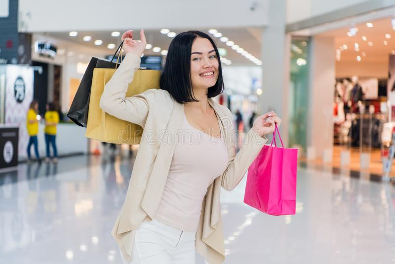 Stående av den härliga unga kvinnan med shoppingpåsar som ut går på en shopping spree arkivfoton