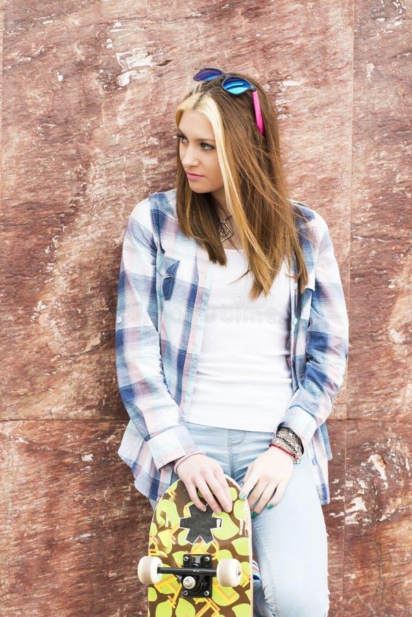 Stående av den härliga unga kvinnan med skateboarden som bort ser royaltyfri fotografi
