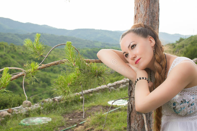 Stående av den härliga unga kvinnan nära tree fotografering för bildbyråer