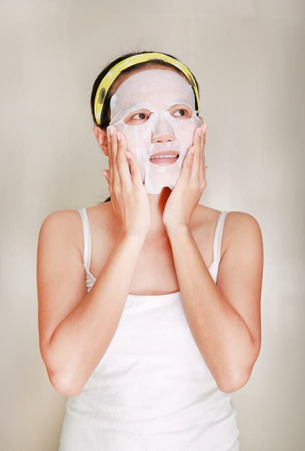 Stående av den härliga unga kvinnan som applicerar den ansikts- maskeringen för föryngring på hennes framsida arkivfoto