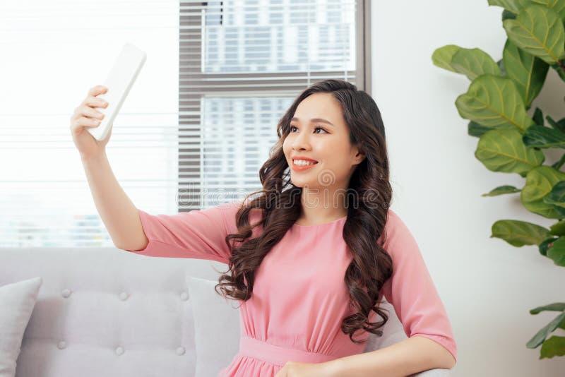 Stående av den härliga unga kvinnan som gör en selfie genom att använda smart ph arkivfoton