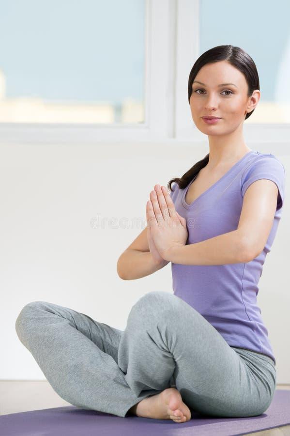 Stående av den härliga unga kvinnan som gör yogaövningen - Meditati arkivfoto