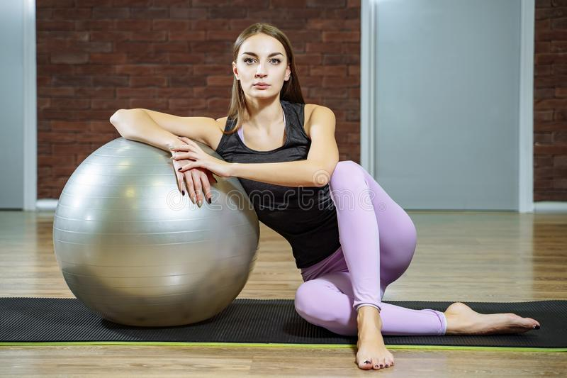 Stående av den härliga unga kvinnan som kopplar av efter konditiongenomkörare i idrottshall arkivfoton