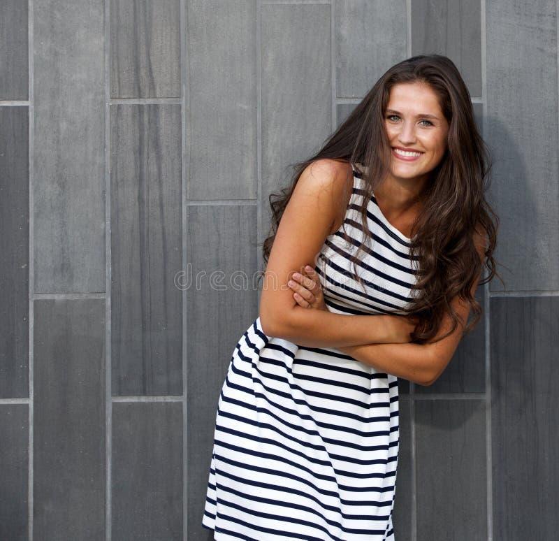 Stående av den härliga unga kvinnan som ler med korsade armar arkivbilder