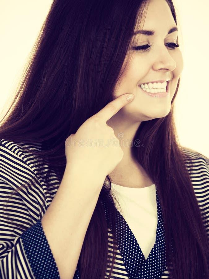 Stående av den härliga unga kvinnan som pekar på tänder fotografering för bildbyråer