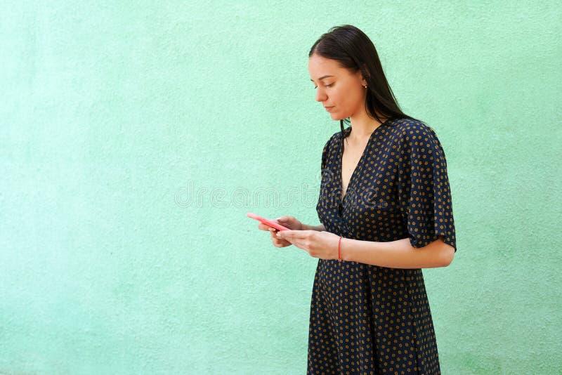 Stående av den härliga unga kvinnan som rymmer den smarta telefonen på grön bakgrund med kopieringsutrymme arkivbilder