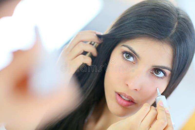 Stående av den härliga unga kvinnan som ser spegeln arkivbilder