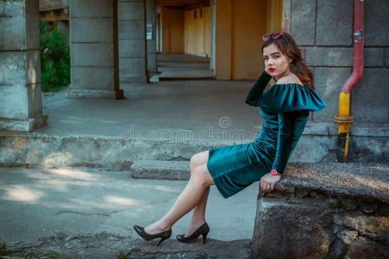 Stående av den härliga unga kvinnan som sitter nära gammal byggnad arkivbilder