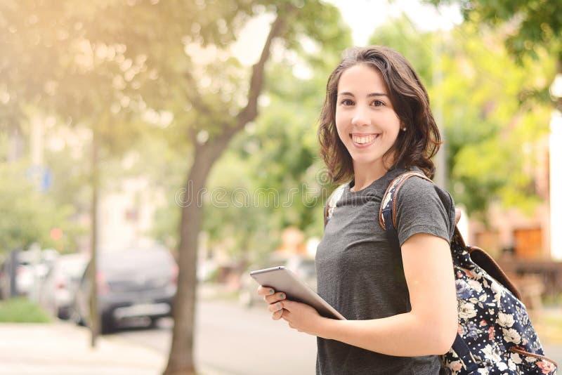 Stående av den härliga unga kvinnan som utomhus använder minnestavlan arkivfoton