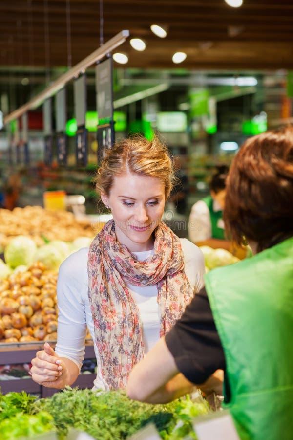 Stående av den härliga unga kvinnan som väljer den gröna lövrika grönsaken royaltyfri fotografi