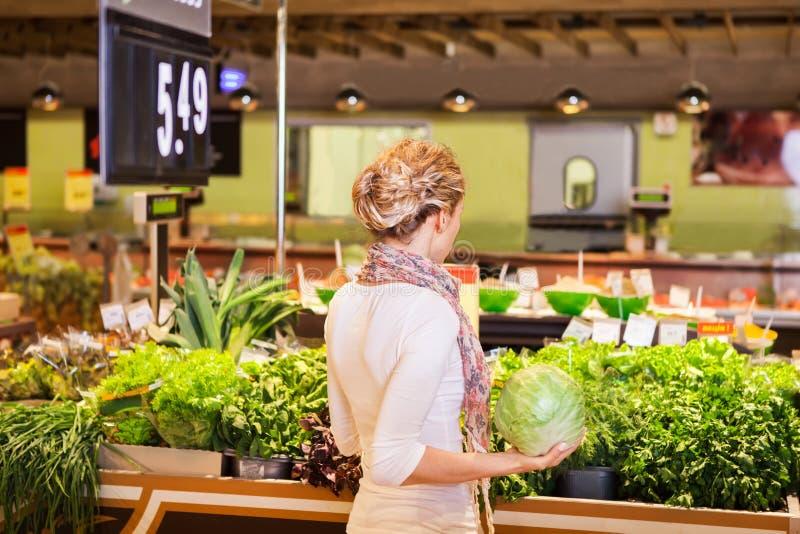 Stående av den härliga unga kvinnan som väljer den gröna lövrika grönsaken royaltyfri foto
