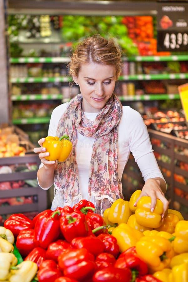 Stående av den härliga unga kvinnan som väljer grönsaker i livsmedelsbutik royaltyfri foto