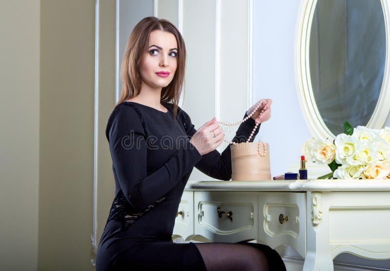 Stående av den härliga unga le brunettkvinnan som sitter nära spegeln arkivbilder
