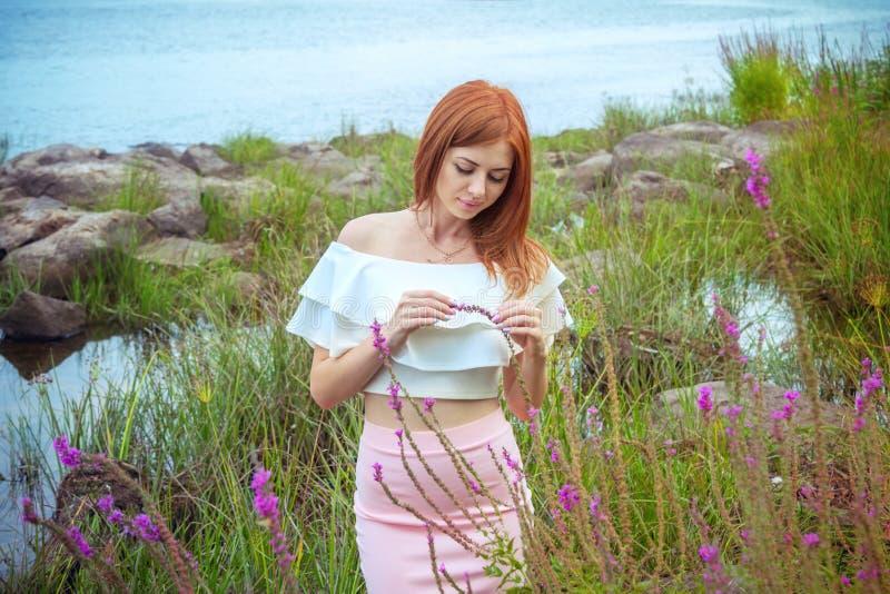 Stående av den härliga unga ledsna kvinnan med långt rött hår arkivfoto