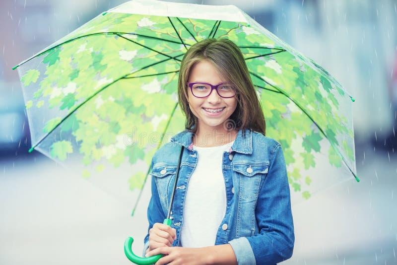 Stående av den härliga unga pre-tonåriga flickan med paraplyet under regn royaltyfri fotografi