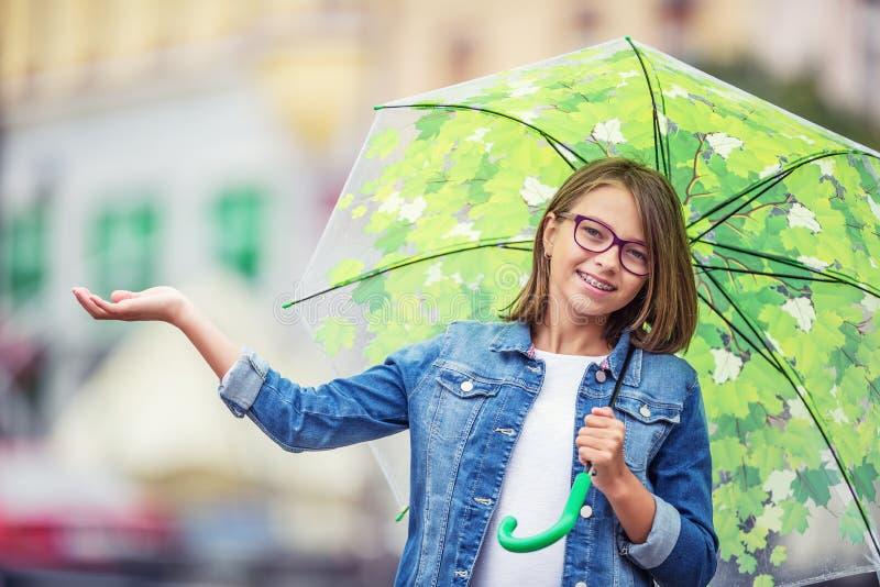 Stående av den härliga unga pre-tonåriga flickan med paraplyet under regn royaltyfria foton