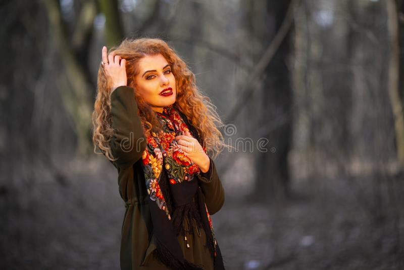 St?ende av den h?rliga unga r?da Haired kvinnan i Olive Coat Posera i Forest Outdoors royaltyfri bild