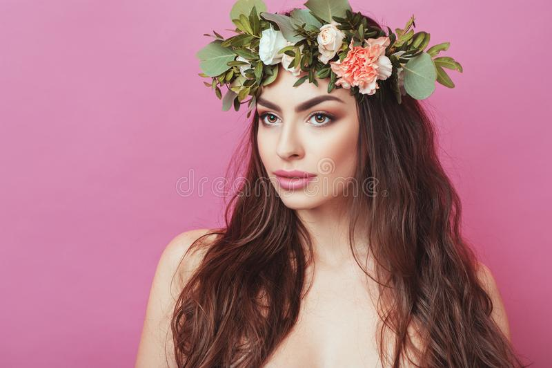 Stående av den härliga unga sexuella sinnliga kvinnan med det perfekta hudsminket som strömmar hår och blommor på huvudet på rosa arkivbilder