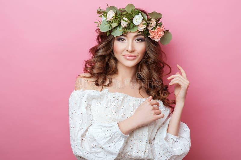 Stående av den härliga unga sexuella sinnliga kvinnan med hår och blommor för perfekt hudsmink lockigt på huvudet på rosa bakgrun royaltyfri foto