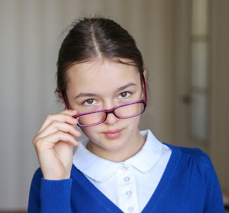 Stående av den härliga unga skolflickan i skolalikformign som ser över överkanten av hennes exponeringsglas arkivbilder