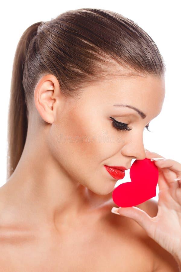 Stående av den härliga ursnygga le kvinnan med ljus makeup för glamour och röd hjärta i hand fotografering för bildbyråer
