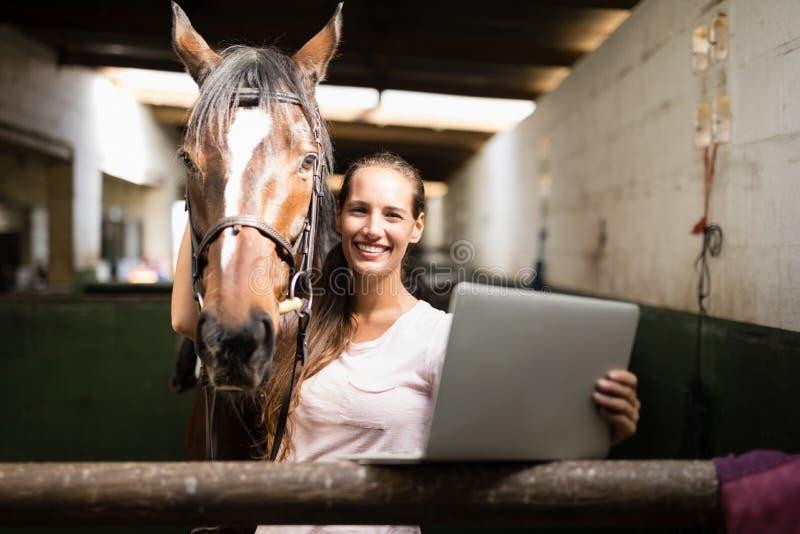 Stående av den hållande bärbara datorn för kvinnlig jockey, medan stå vid hästen royaltyfria bilder