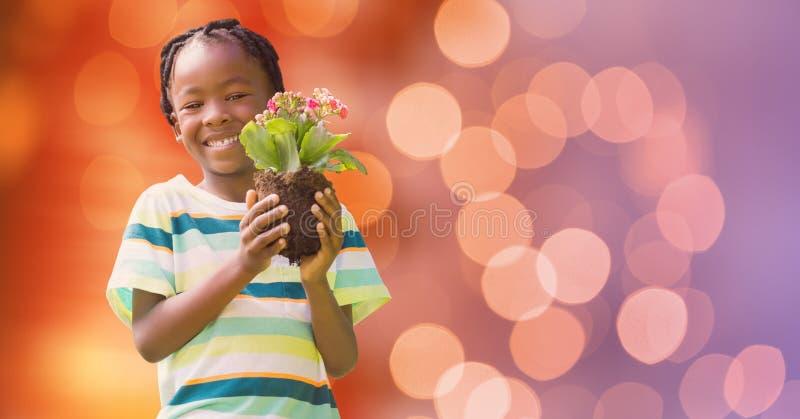 Stående av den hållande blomkrukan för lycklig pojke över bokeh royaltyfri fotografi