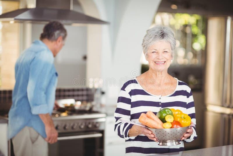 Stående av den hållande durkslaget för lycklig hög kvinna med grönsaker fotografering för bildbyråer