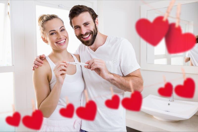 Stående av den hållande graviditetstestet för lyckliga par i badrum royaltyfri bild