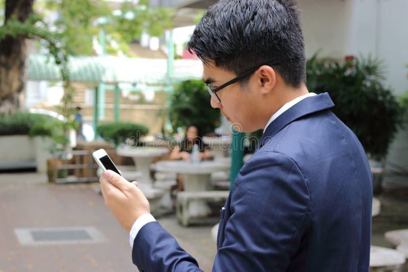 Stående av den hållande mobila smartphonen för affärsman i parkera royaltyfri fotografi