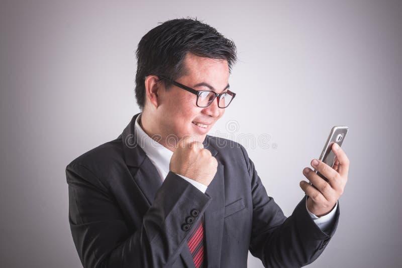 Stående av den hållande smartphonen för asiatisk affärsman Lyckligt eller excit arkivfoton