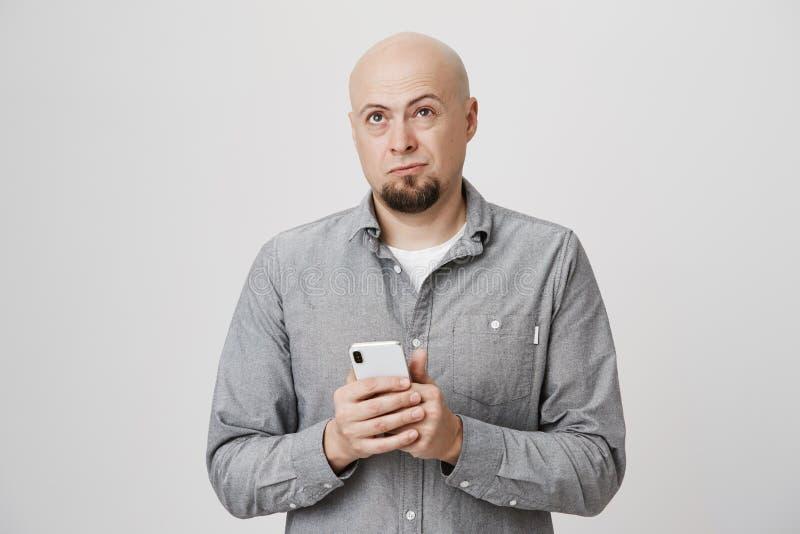 Stående av den hållande smartphonen för stilig skallig europeisk grabb, medan rynka pannan och se upp som försöker att återkalla  royaltyfri foto