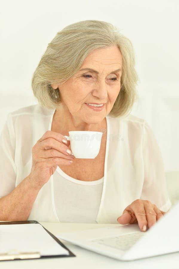 Stående av den höga affärskvinnan som arbetar med bärbara datorn royaltyfri foto