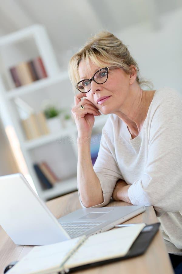 Stående av den höga affärskvinnan som arbetar på laprop arkivbild