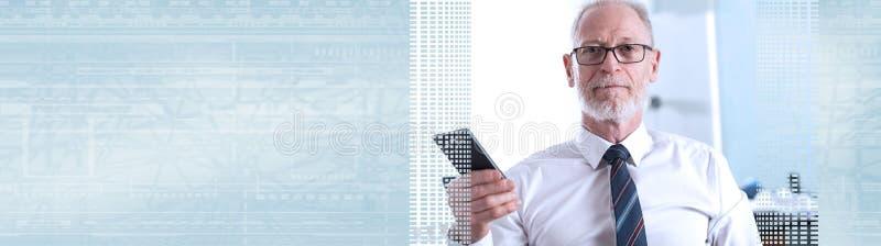 Stående av den höga affärsmannen som rymmer hans mobiltelefon; panorama- baner royaltyfri bild