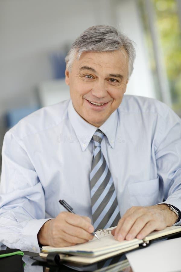 Stående av den höga affärsmannen som wiriting i dagordning arkivfoton