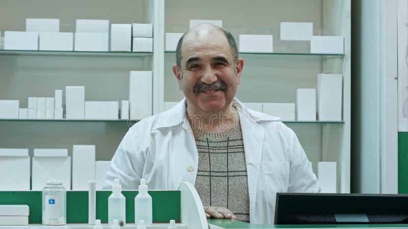 Stående av den höga apotekaren som ler och talar till en kamera royaltyfria bilder