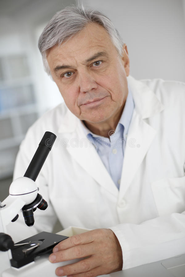 Stående av den höga doktorn som ser till och med mikroskopet royaltyfri foto