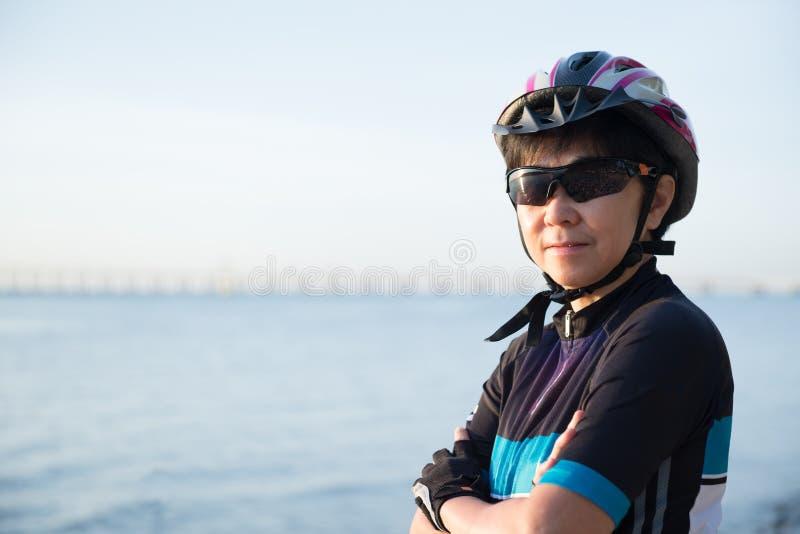 Stående av den höga kvinnacyklisten royaltyfria bilder