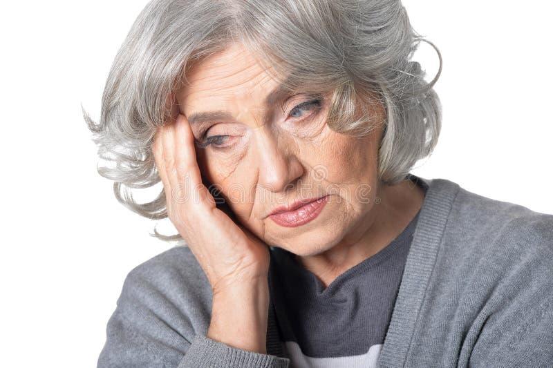 Stående av den höga kvinnan i grå blus med huvudvärk på vit bakgrund fotografering för bildbyråer