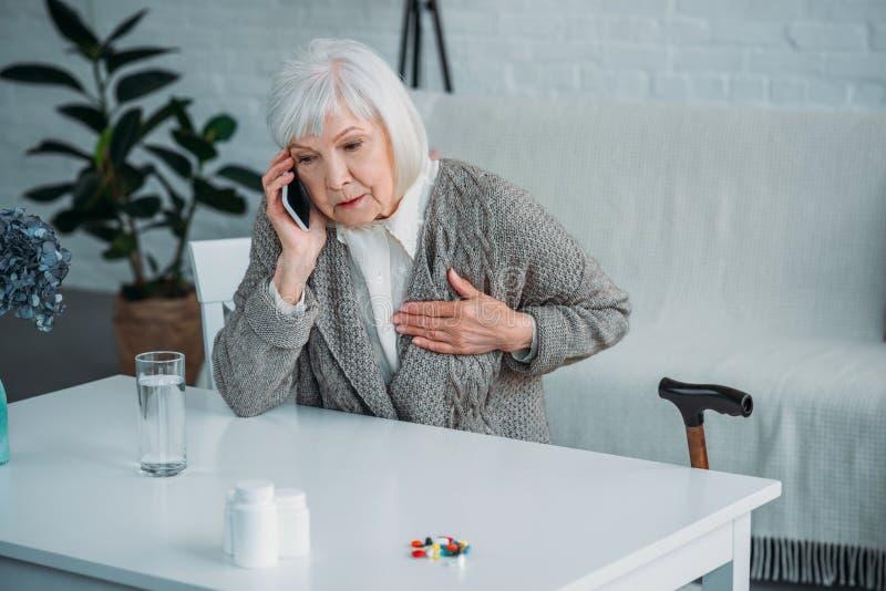 stående av den höga kvinnan med hjärtaknip som talar på smartphonen på tabellen med mediciner royaltyfri bild