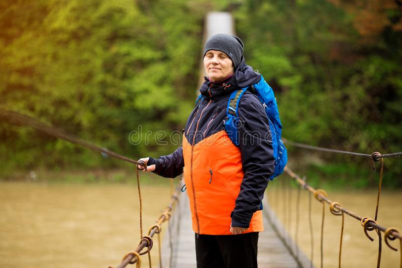 Stående av den höga kvinnan med ryggsäcken på den arga floden för vandring royaltyfri foto