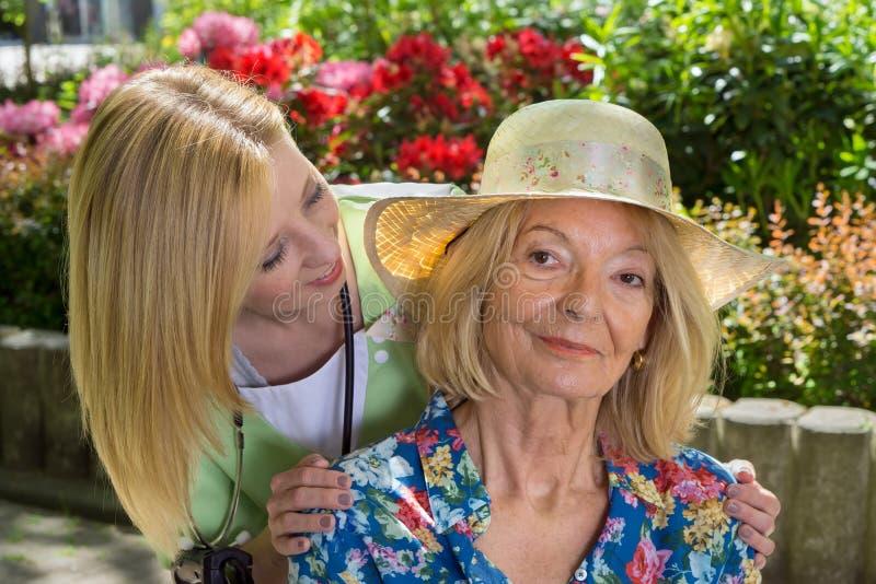 Stående av den höga kvinnan med sjuksköterskan Outdoors arkivfoto