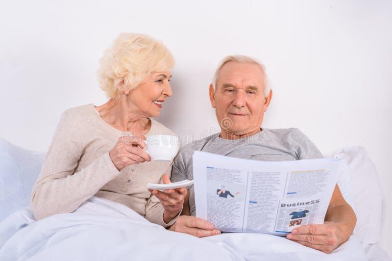 stående av den höga kvinnan som dricker kaffe medan läs- tidning för make i säng royaltyfri foto
