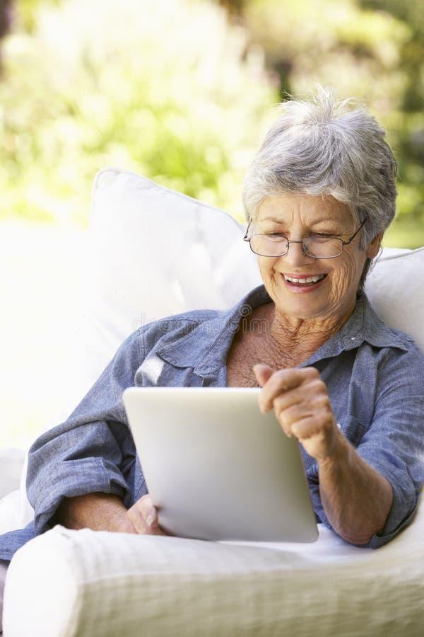 Stående av den höga kvinnan som hemma använder den Digital minnestavlan royaltyfria foton