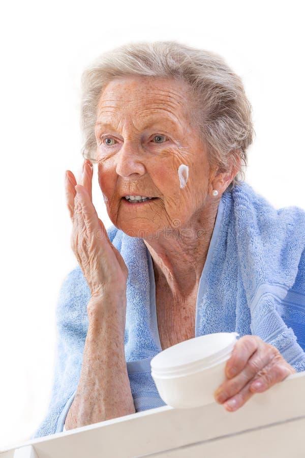 Stående av den höga kvinnan som sätter på anti--åldras kräm på hennes framsida mot vit bakgrund Anti--åldras begrepp, royaltyfria bilder