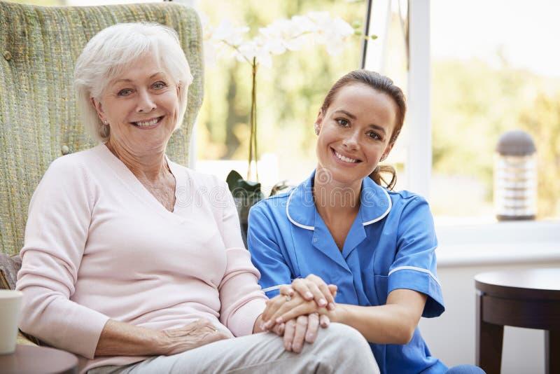 Stående av den höga kvinnan som sitter i stol med sjuksköterskan In Retirement Home royaltyfria foton